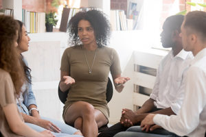 counselor talks to two male and two female patients about anxiety treatment programs